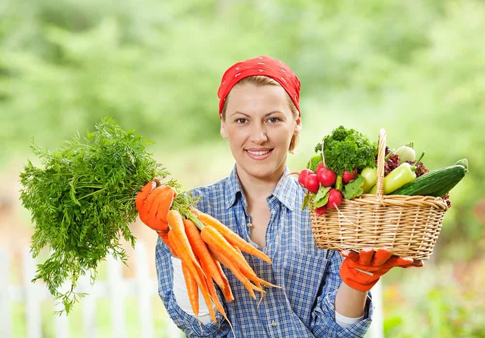 Women holding a selection of fresh vegetables